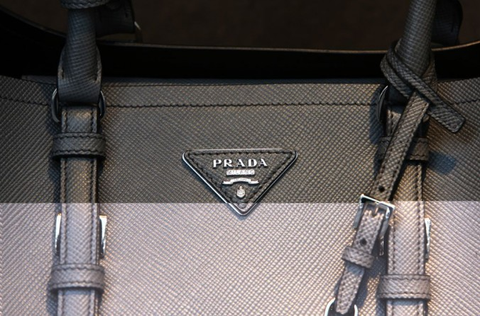 A Prada logo sits on the side of a women's bag displayed for sale in the window Prada SpA luxury store on Sloane Street in London, U.K., on Wednesday, Sept. 24, 2014. The pound rose to the strongest level in two years versus the euro amid bets the Bank of England is moving closer to increasing interest rates as its euro-area counterpart boosts stimulus. Photographer: Chris Ratcliffe/Bloomberg via Getty Images Inspirations from Prada Inspirations from Prada Inspirations from Prada luxury goods e1457082786302